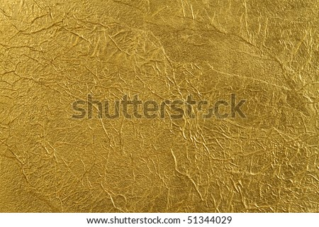 texture of the wall, covered with a thin gold foil, with beautiful folds and fissures - stock photo