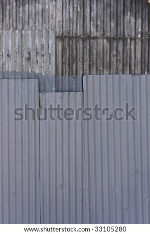 Texture of weathered corrugated sheets of steel riveted together - stock photo