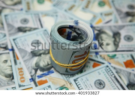texture spilling hundred dollar bills. dollar roll on background of many dollars - stock photo