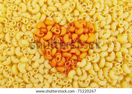 Texture units of the yellow and orange pasta with the image of the heart in the middle - stock photo