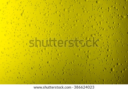 Texture water drops on the yellow bottle close-up as a background. - stock photo