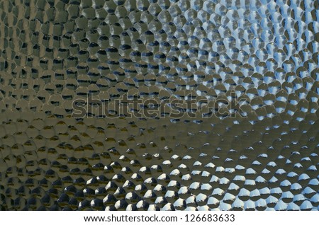 Textured glass panel with strong highlights and deep shadows - stock photo