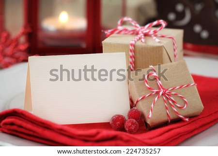 Textured greeting card with copy space for your own text on a plate with wrapped Christmas presents with a lantern and gingerbread cookies at the background as a concept of a festive dinner - stock photo