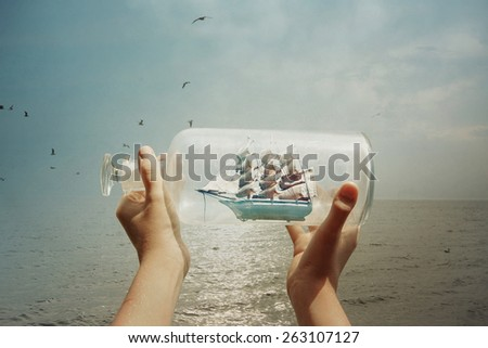 Textured image of a child holding a ship in a bottle at the ocean - stock photo