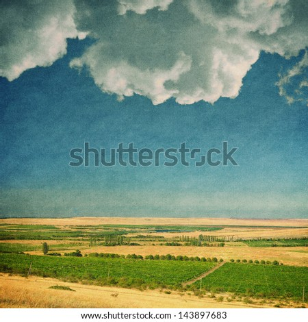 textured old paper background with field and sky - stock photo