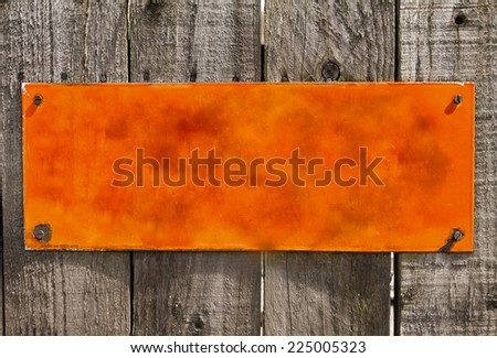 Textured  orange  rusty metal background, blank surface for your text. Screwed to rough wood panel fence - stock photo