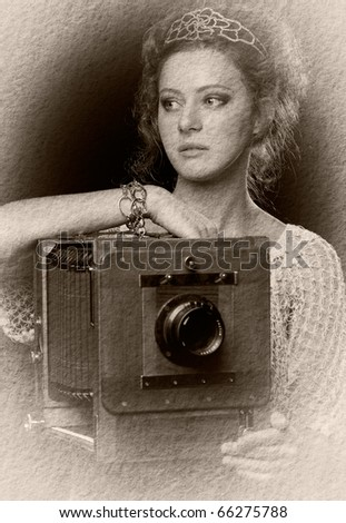 Textured retro photo of young woman standing near the old camera - stock photo