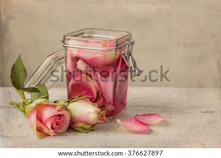 Textured still life of rose water and roses on a painterly background - stock photo