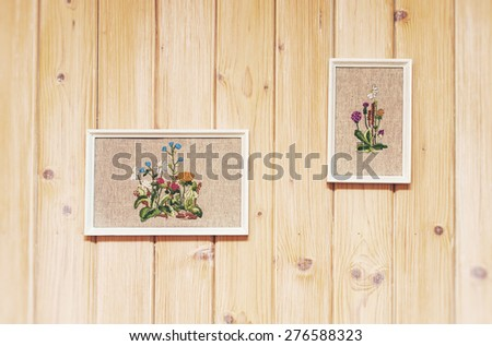 Textured wooden wall with embroidered pictures. - stock photo