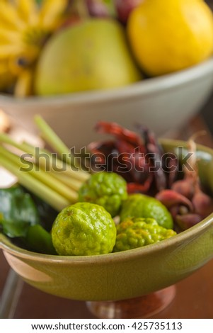 Thai and asian food ingredients in bowls, bergamot orange, dried chili, lemons, limes, lemongrass, banana, pomelo, selective focus on the closest bergamot orange at the lower part of the photo - stock photo
