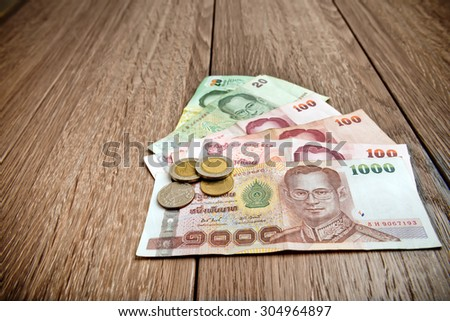 Thai banknote and coins on table - stock photo