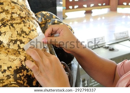 Thai Buddhist People doing cover Statue of Buddha with Gold Leaf.  This is Tradition Culture of Thai Buddhist. - stock photo