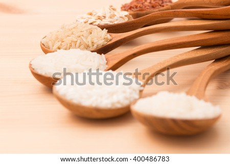 Thai cargo rice is the creation of thai rice eaperts and Japanese Brown rice, Glutionus Mixed whole grain traditional thai rices best rices for healthy  in wood spoon on a weathered wood background - stock photo