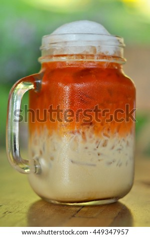 Thai cold milk tea was put in a glass with a handle. - stock photo