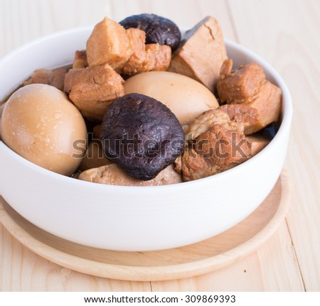Thai Cuisine , Boiled eggs with chicken drumstick and fried tofu in sweet gravy soup seasonings top with coriander.Eggs and pork in brown sauce frogs. - stock photo