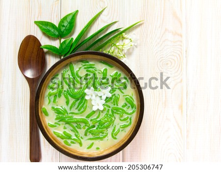 Thai dessert, rice noodles made of rice eaten with coconut milk on wooden table, Top view  - stock photo