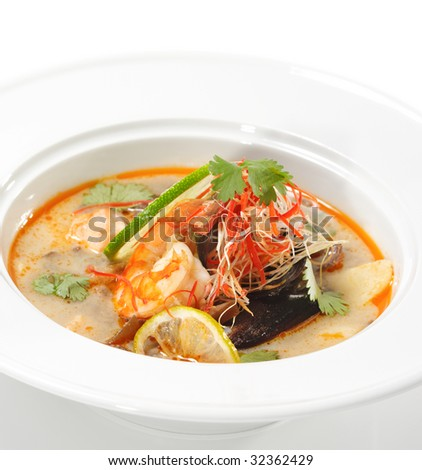 Thai Dishes - Tom Yam Kung. Spicy Shrimp Soup with Coconut milk, Lime and Seafood - stock photo