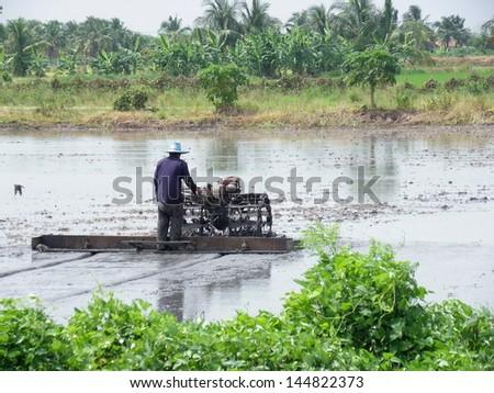 thai farmer driving  tractor - stock photo