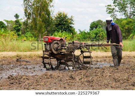 Thai farmer using walking tractors for cultivated soil for rice  - stock photo