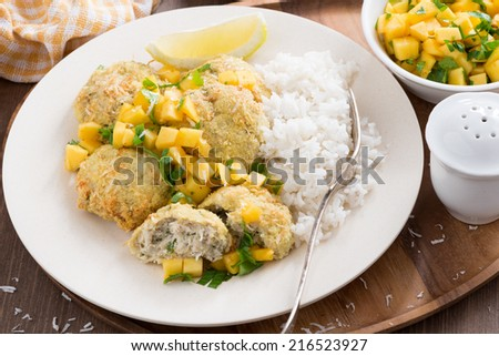 Thai fish cakes with mango salsa and rice, top view - stock photo