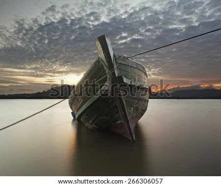 Thai fishery boat has retried and strand on the beach. - stock photo