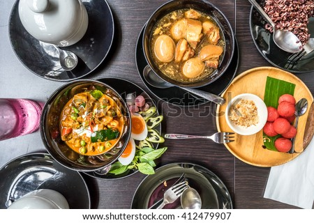 Thai Food: Flat lay of Panang (Thai Red Curry), Palo (Thai Five Spices Egg and Pork Soup), Watermelon snack and brown rice - stock photo
