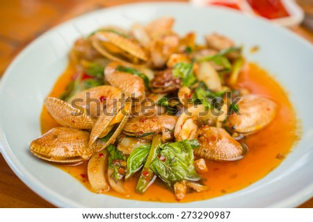 Thai fried sea shells with spicy sauce on table in restaurant - stock photo