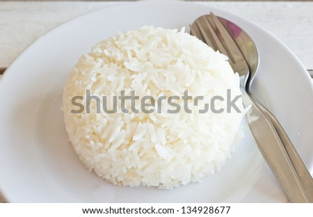 Thai jasmine cooked  rice on white plate - stock photo