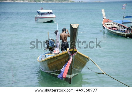 Thai man inspect and repair wooden fishery boat floating and stop wait for fishing in evening time at Rawai beach at andaman ocean at Phuket, Thailand - stock photo