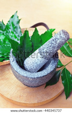 Thai medicinal herb neem leaves on mortar and pestle in bamboo box with wooden background. - stock photo