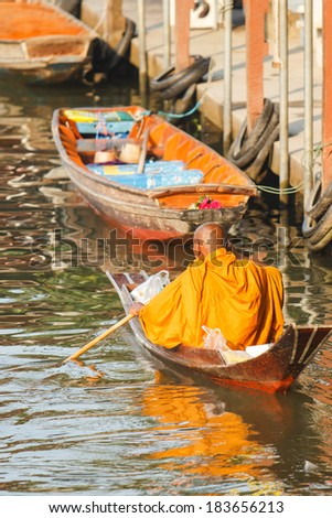 Thai monk paddle wooden boat in morning, Thailand - stock photo