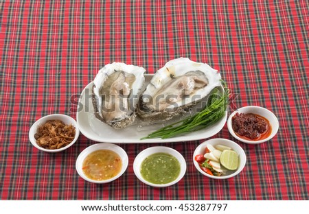 Thai oyster, served with roasted onion, Thai lime, chili, Thai spicy paste, and two types of spicy dip - stock photo