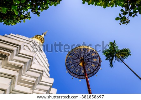 Thai pagoda, golden umbrella & palm tree against blue sky at Buddhist temple in Chiang Mai, northern Thailand - stock photo