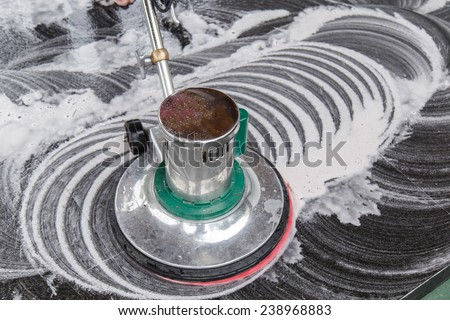 Thai people cleaning black granite floor with machine and chemical - stock photo