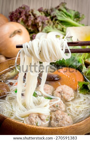 Thai ramen noodle on table with garnish and vegetables. - stock photo