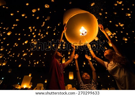Thai's Family release sky lanterns to worship buddha's relics in yi peng festival, Chiangmai thailand - stock photo