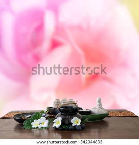 Thai spa massage setting herbal compress balls, essential oil bottle, frangipani and incense on  rose , soft focus motion blur background - stock photo