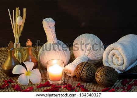 thai spa massage setting with towel, frangipani, herbal compress balls, candle, aroma reed diffuser and rose petals - stock photo