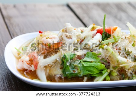 Thai Spicy noodle salad or Spicy vermicelli salad with shrimp, squid, pork chop. - stock photo