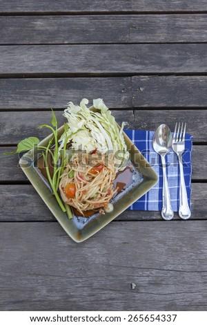 Thai spicy papaya salad on old wood floor vertical - stock photo