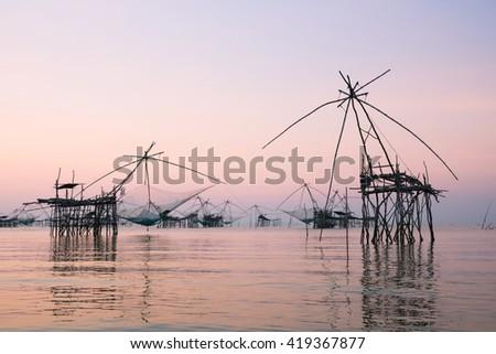 Thai style fishing trap in Pak Pra Village, Net Fishing Thailand,silhouette. - stock photo