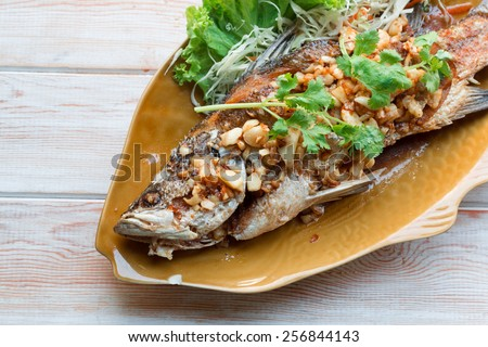 Thai style food main course: whole fried sea bass with garlic  - stock photo