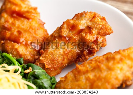 Thai style fried chicken wings on a round white plate with egg noodles and spinach. Close up with shallow depth of field. - stock photo