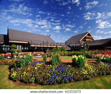 Thai style house and flower garden - stock photo