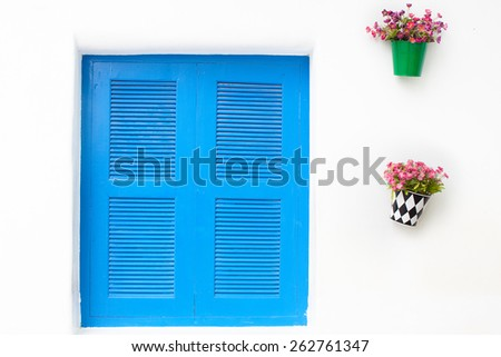 thai style window. Blue on white wall with closed shutters - stock photo