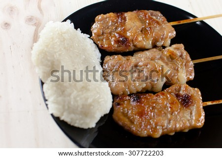 Thai-styled grilled pork and sticky rice. It's among most popular street foods in Thailand - stock photo