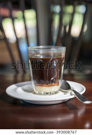 Thai tradition hot coffee with sweetened condensed milk in old style cup, served on wooden table. - stock photo