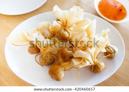 Thai traditional appetisers (Toong Tong), spring rolls served with sweet chilli sauce. - stock photo