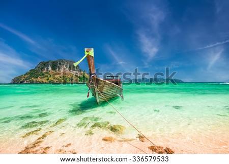 Thai traditional wooden boat with ribbon decoration at ocean shore near Koh Tup island. Thailand, Krabi province, Ao Nang - stock photo