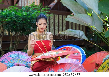 Thai Woman In Traditional Costume Of Thailand painting umbrella - stock photo